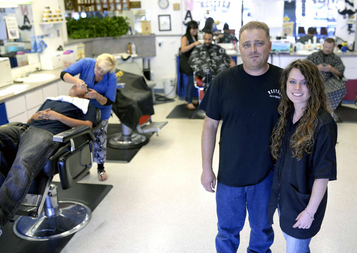 Co-owners Chris and Jennifer Hodge in portrait at the Western Barber and Gun Store on Wednesday, August 19, 2015. The barbershop occupies the front of the storefront and the gun shop is tucked into a small room near the back. James Durbin/Reporter-Telegram