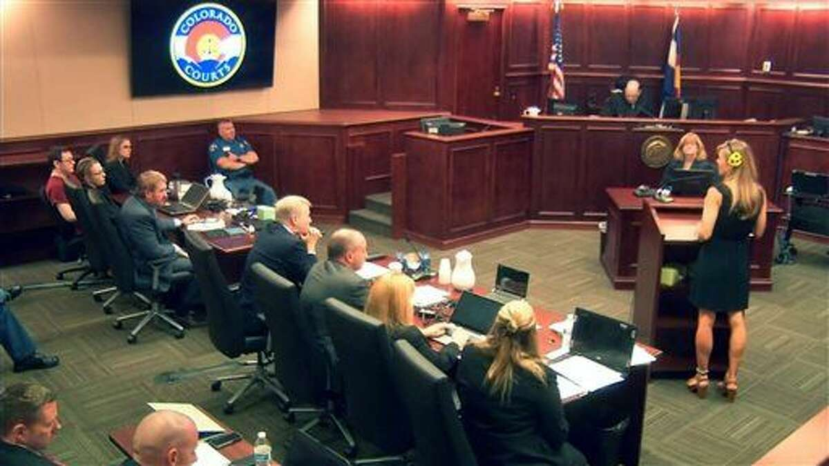 In an image made from video, Colorado theater shooter James Holmes, far left, sits at the defense table during a statement reading by Kathleen Pourciau, far right, the mother of surviving theater shooting victim Bonnie Kate Pourciau-Zoghbi, during the final sentencing phase of the Holmes trial in Centennial, Colo., Monday, Aug. 24, 2015. Holmes was convicted Aug. 7 of murdering 12 people when he opened fire on a crowded movie theater in 2012. (Colorado Judicial Department via AP, Pool)