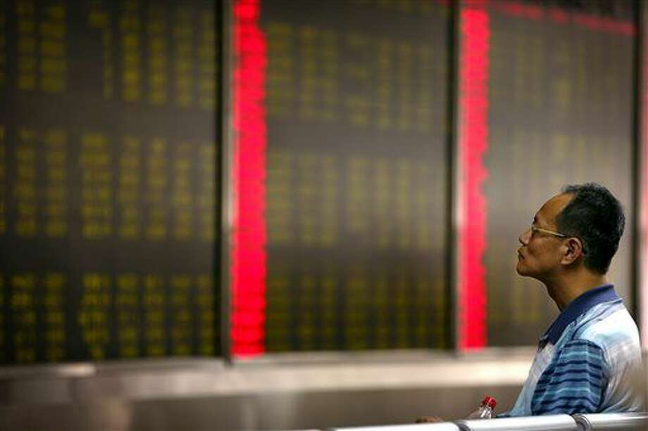 A Chinese investor monitors stock prices at a brokerage house in Beijing, Monday, Aug. 24, 2015. Stocks tumbled across Asia on Monday as investors shaken by the sell-off last week on Wall Street unloaded shares in practically every sector. (AP Photo/Mark Schiefelbein) Photo: Mark Schiefelbein