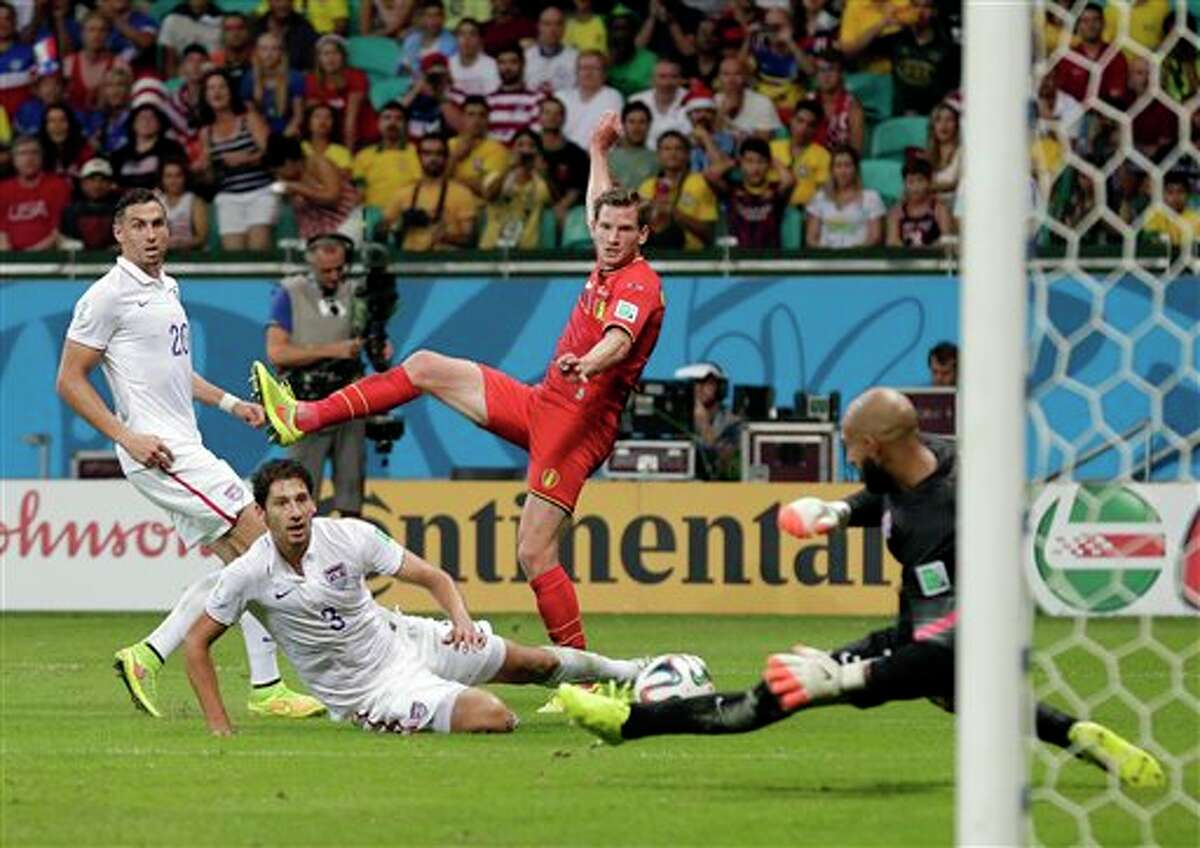 United States' Omar Gonzalez (3) and Geoff Cameron (20) watch as goalkeeper Tim Howard makes a save on Belgium's Jan Vertonghen shot on goal during the World Cup round of 16 soccer match between Belgium and the USA at the Arena Fonte Nova in Salvador, Brazil, Tuesday, July 1, 2014. (AP Photo/Marcio Jose Sanchez)