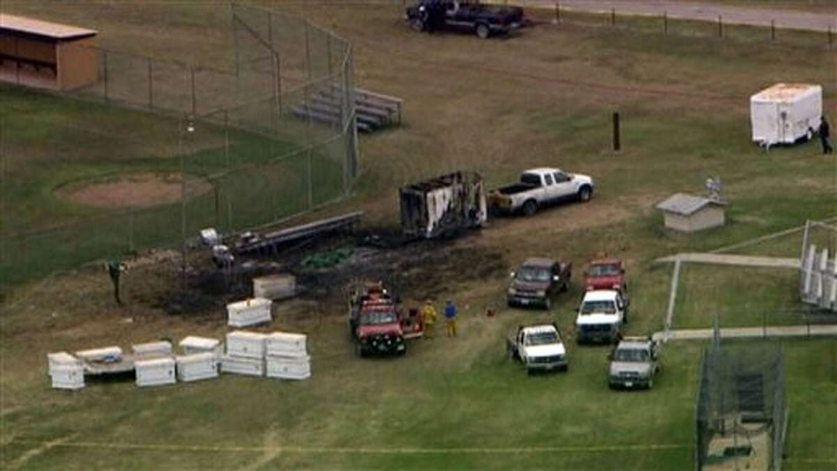 This photo from video provided by WFAA-TV in Dallas shows the aftermath of a fireworks explosion in Comanche, Texas, Thursday, July 3, 2014. A trailer loaded with fireworks exploded near a Texas high school, killing one person and injuring three other people who were setting up for a Fourth of July show. It's unclear what triggered the explosion, which occurred near a baseball field adjacent to the high school in Comanche, about 100 miles southwest of Fort Worth. The trailer was hooked to a pickup truck.(AP Photo/WFAA-TV) TELEVISION OUT