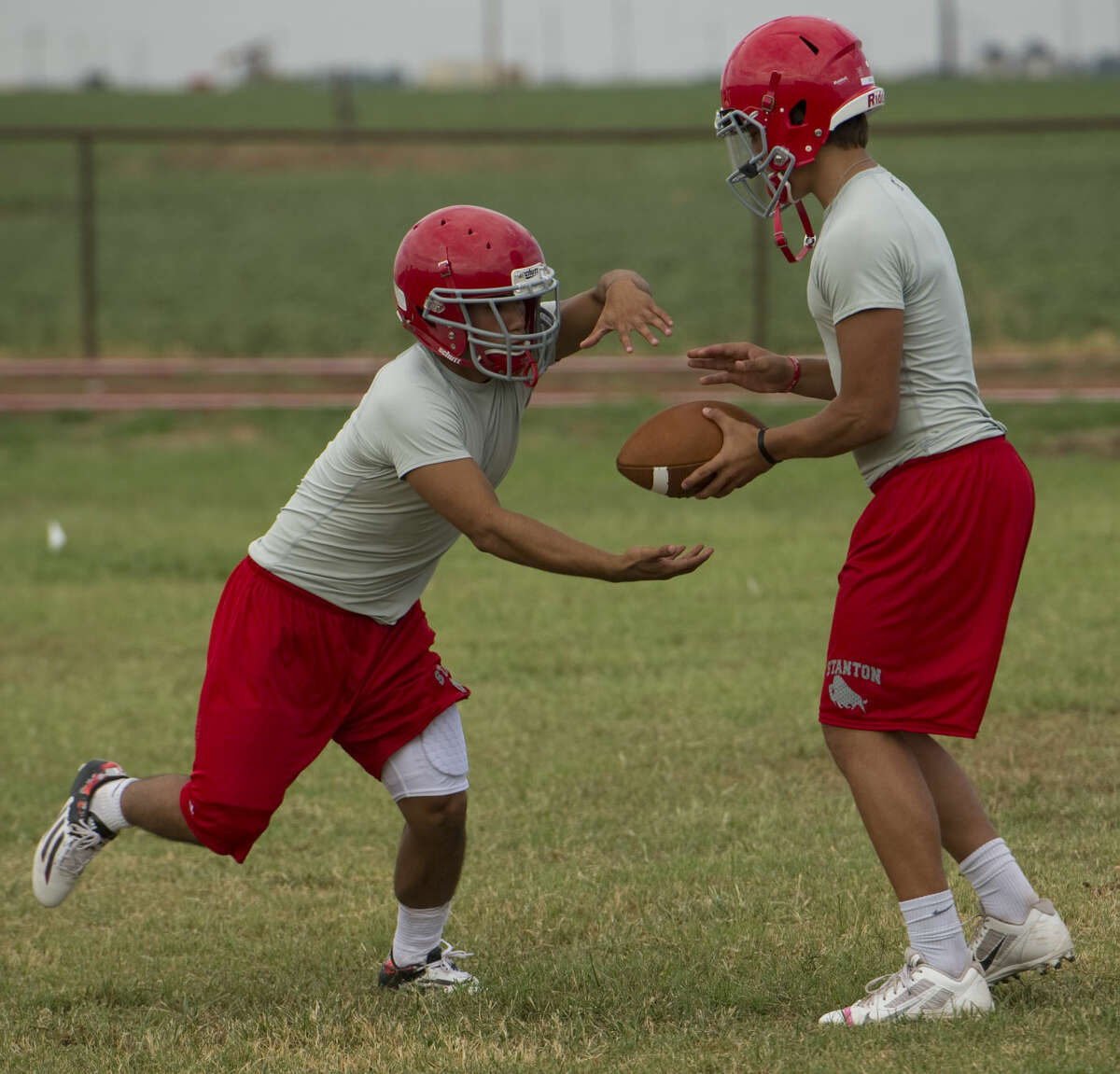 Stanton running back Estevan Chavez takes a handoff from Tristan Graves as they and other players run drills Tuesday 8-4-15, during the first week of football practice. Tim Fischer\Reporter-Telegram