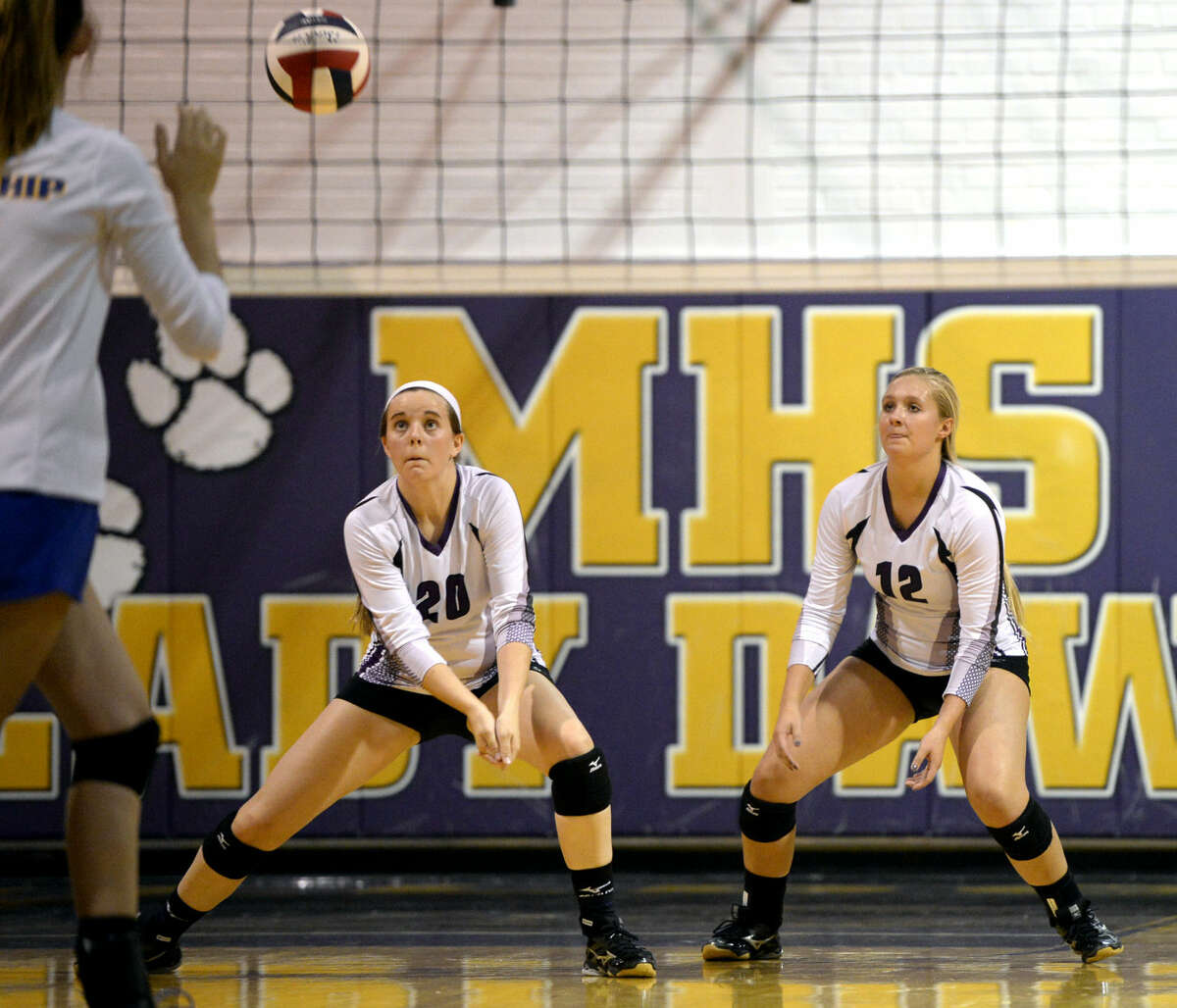 Midland High's Claire Lancaster (20) and Christen Beckham (12) react to a hit from Wolfforth Frenship on Tuesday, September 1, 2015 at Midland High. James Durbin/Reporter-Telegram