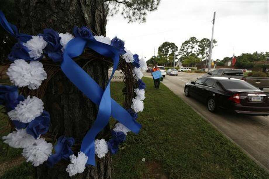 A car passes by a wreath that rests across the street from a gas station where Deputy Darren Goforth was fatally shot Tuesday, Sept. 1, 2015, in Houston. Godforth was shot while at a gas station. The man accused of fatally shooting the suburban Houston officer was committed to mental health facilities in the last five years and his attorney said Tuesday the man will undergo a psychological evaluation. (Steve Gonzales/Houston Chronicle via AP) MANDATORY CREDIT Photo: Steve Gonzales