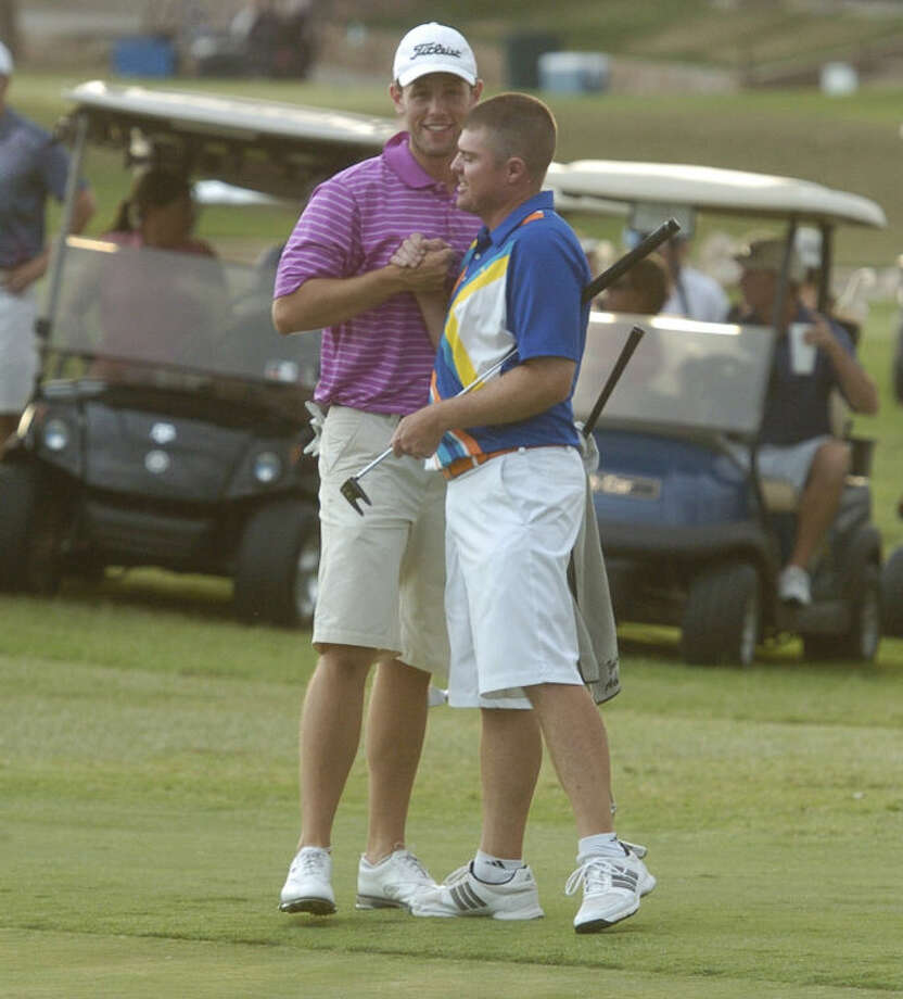 Zach Atkinson, left, is congratulated by his partner Michael Pruitt, right, after the two clinched the 2013 Jamboree championship on the 18th hole on Sunday at Green Tree Country Club. The pair shot a 59 on the final day to win by two shots over Terene Begnel and Brady Shivers. Len Hayward/Reporter-Telegram