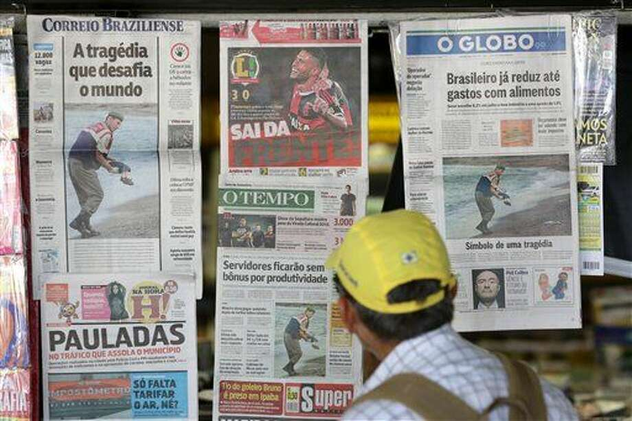 Brazilian newspaper covers show the photo of the dead 3-year-old Syrian boy on a Turkish beach, at a news stand in Brasilia, Brazil, Thursday, Sep. 3, 2015. The photo of the body washed up on the sand was splashed on the front of all major newspapers in Brazil, a nation with more homicides than any other, according to the United Nations. Still, the picture ignited despair and indignation. (AP Photo/Eraldo Peres) Photo: Associated Press
