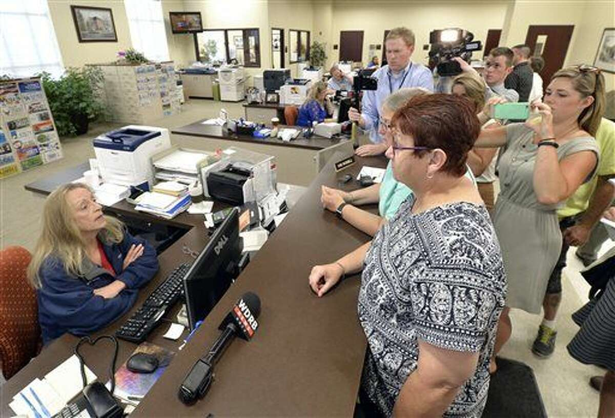 Karen Roberts, center, and her partner April Miller speak with Rowan County Clerk Kim Russell in an attempt to obtain a marriage license at the Rowan County courthouse in Morehead, Ky., Thursday, Aug. 13, 2015. Miller and Roberts, two of the original plaintiffs in the federal suit against Rowan County, Ky., and Rowan County Clerk Kim Davis were at the courthouse to obtain a marriage license. The clerk's office rejected the couples' bid for licenses just hours after U.S. District Judge David L. Bunning ordered Davis to comply with the Supreme Court's ruling. (AP Photo/Timothy D. Easley)