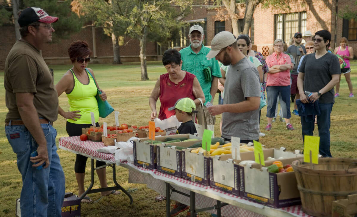 Brandon Dieringer looks on as customers line up Saturday 8-15-2015 at the Dieringer Farms table at the Midland Farmer's Market. Tim Fischer\Reporter-Telegram