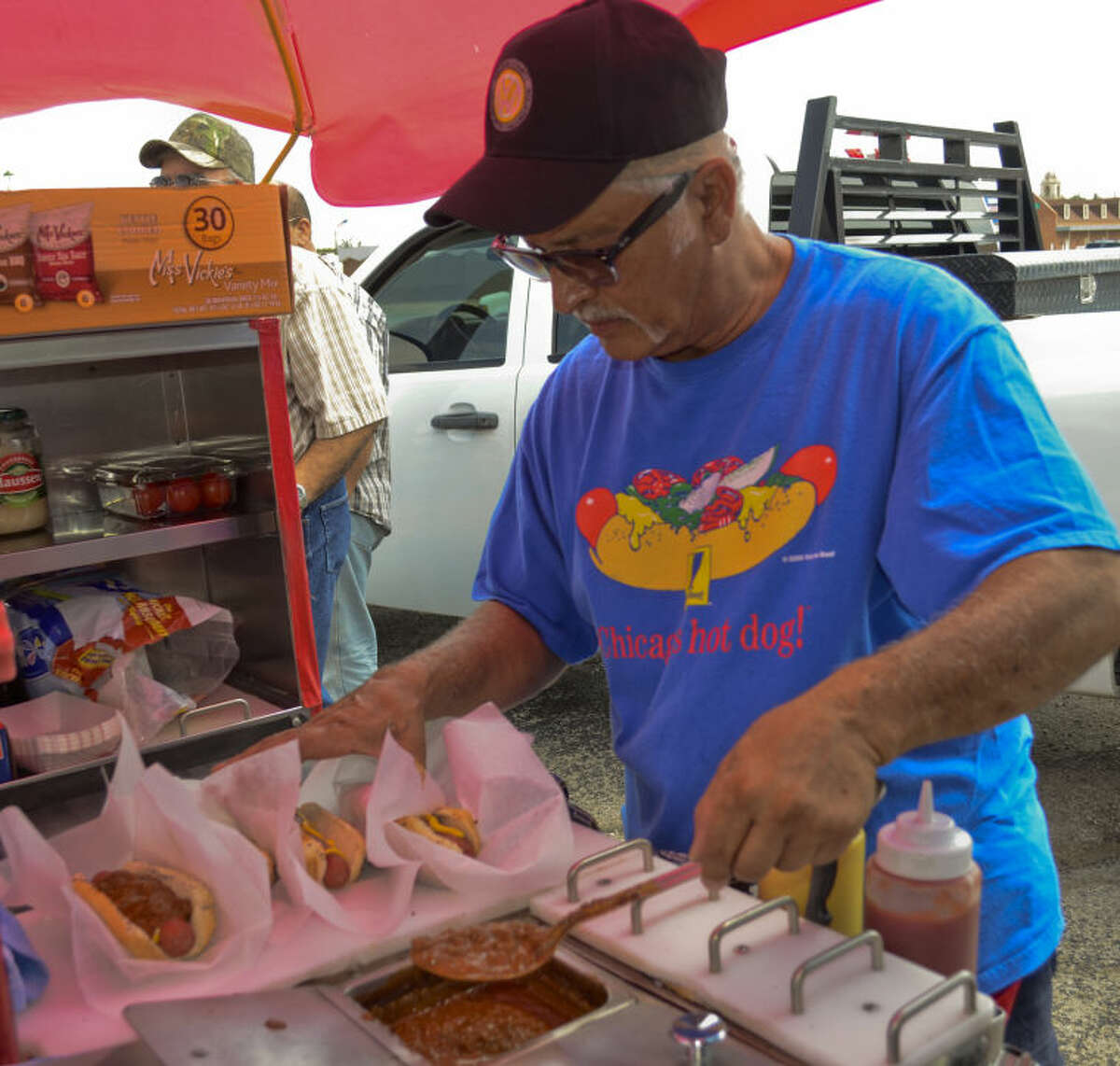 Ric Beltran, who owns and runs Dogmatic hot dog stand from his VW bus, serves up hotgogs with chilli and cheese Wednesday afternoon in Midland. Tim Fischer\Reporter-Telegram
