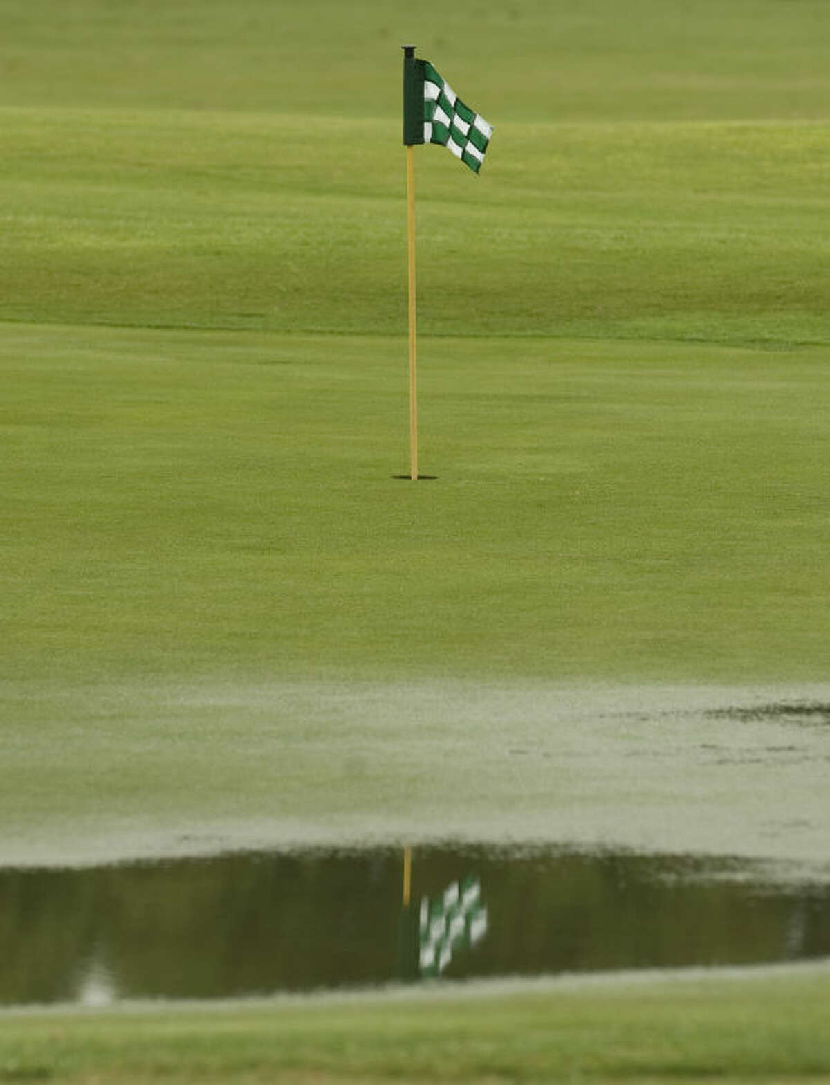 Rain puddles on the putting green at Greentree Country Club Thursday morning. Passing thunderstorms with lightening delayed the Women's City Golf tournament and scattered showers dampened the course and players. Tim Fischer\Reporter-Telegram