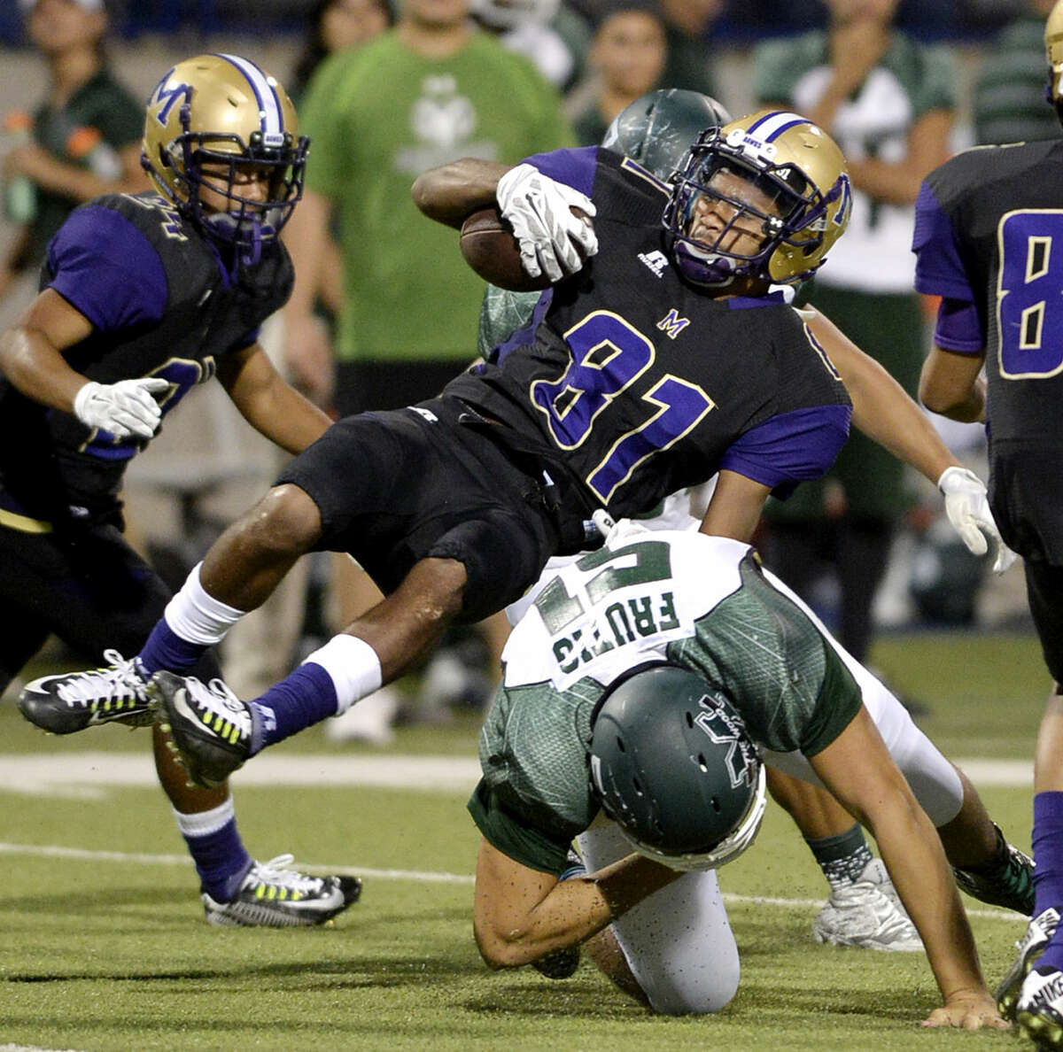 Midland High wide receiver Courtney McMaryion (81) is stopped by El Paso Montwood's Phillip Frutig (51) on Friday, Sept. 4, 2015, at Grande Communications Stadium. James Durbin/Reporter-Telegram