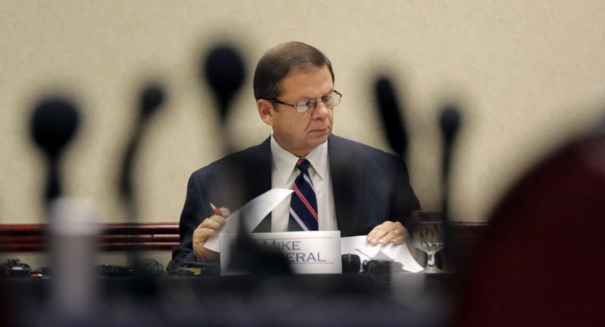 Mike Motheral, chairman of the University Interscholastic League (UIL) State Executive Committee, is seen through a cluster of microphones during an emergency meeting, Wednesday, Sept. 9, 2015, in Round Rock, Texas. The UIL, the governing body for high school sports in Texas, called the meeting to investigate two John Jay High School football players that hit a referee and the surrounding events. (AP Photo/Eric Gay)