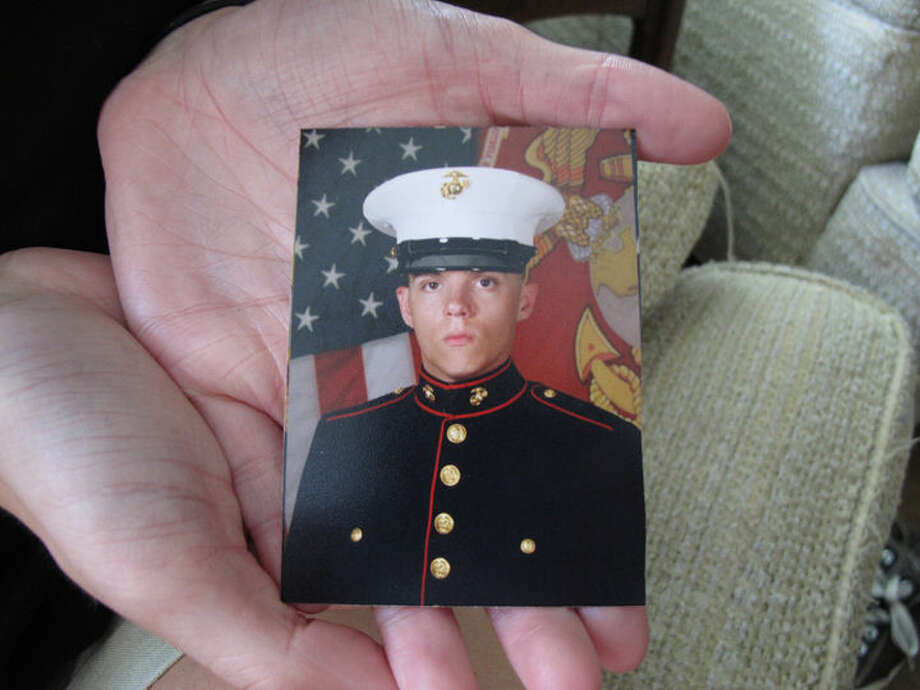 Caroline Dove holds a photo of Marine Corps Lance Cpl. Skip Wells, her boyfriend, in her hands July 17, 2015, at her home in Savannah, Ga. Wells was among four Marines killed July 16, 2015, in an attack at a military training facility in Chattanooga, Tenn. Muhammad Youssef Abdulazeez opened fire Thursday, July 16, 2015, on two U.S. military sites in Chattanooga in an attack that left four Marines dead and raised the specter of terrorism on U.S. soil. He was killed by police.(AP Photo/Russ Bynum) Photo: Russ Bynum