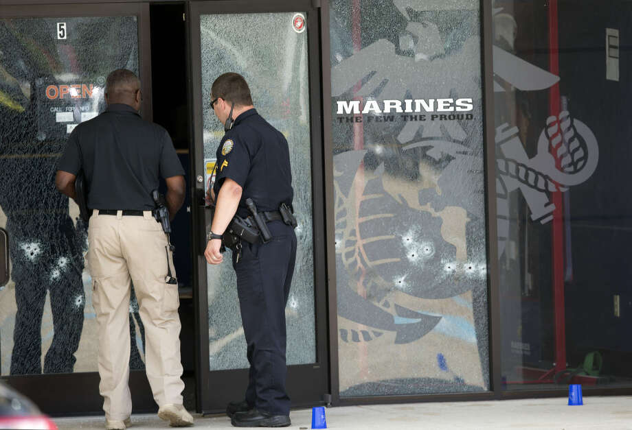 Police officers enter the Armed Forces Career Center through a bullet-riddled door after a gunman opened fire on the building Thursday, July 16, 2015, in Chattanooga, Tenn. Authorities say there were multiple casualties including the gunman. (AP Photo/John Bazemore) Photo: John Bazemore