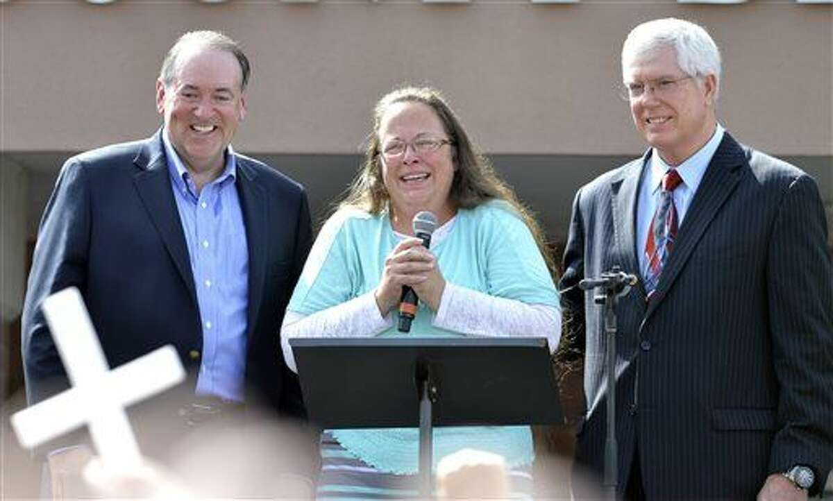 Rowan County Clerk Kim Davis, center with Republican presidential candidate Mike Huckabee, left, and attorney Mat Staver, right, founder of the Liberty Counsel, the Christian law firm representing Davis, at her side, greets the crowd after being released from the Carter County Detention Center, Tuesday, Sept. 8, 2015, in Grayson, Ky. Davis, the Kentucky county clerk who was jailed for refusing to issue marriage licenses to gay couples, was released Tuesday after five days behind bars. (AP Photo/Timothy D. Easley)
