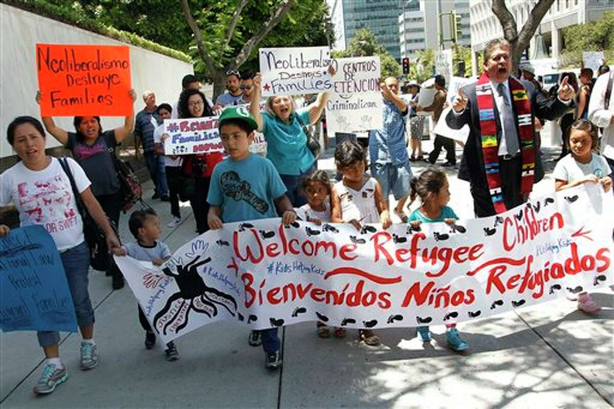 FILE - In this July 7, 2014 file photo, immigrant families and children's advocates rally in response to President Barack Obama's statement on the crisis of unaccompanied children and families illegally entering the United States, outside the Los Angeles Federal building. Tackling what he has called a humanitarian crisis, Obama on Tuesday, July 8, 2014 asked Congress for $3.7 billion to cope with a tide of minors from Central America who are illegally crossing the U.S. border, straining immigration resources and causing a political firestorm in Washington. (AP Photo/Nick Ut, File)