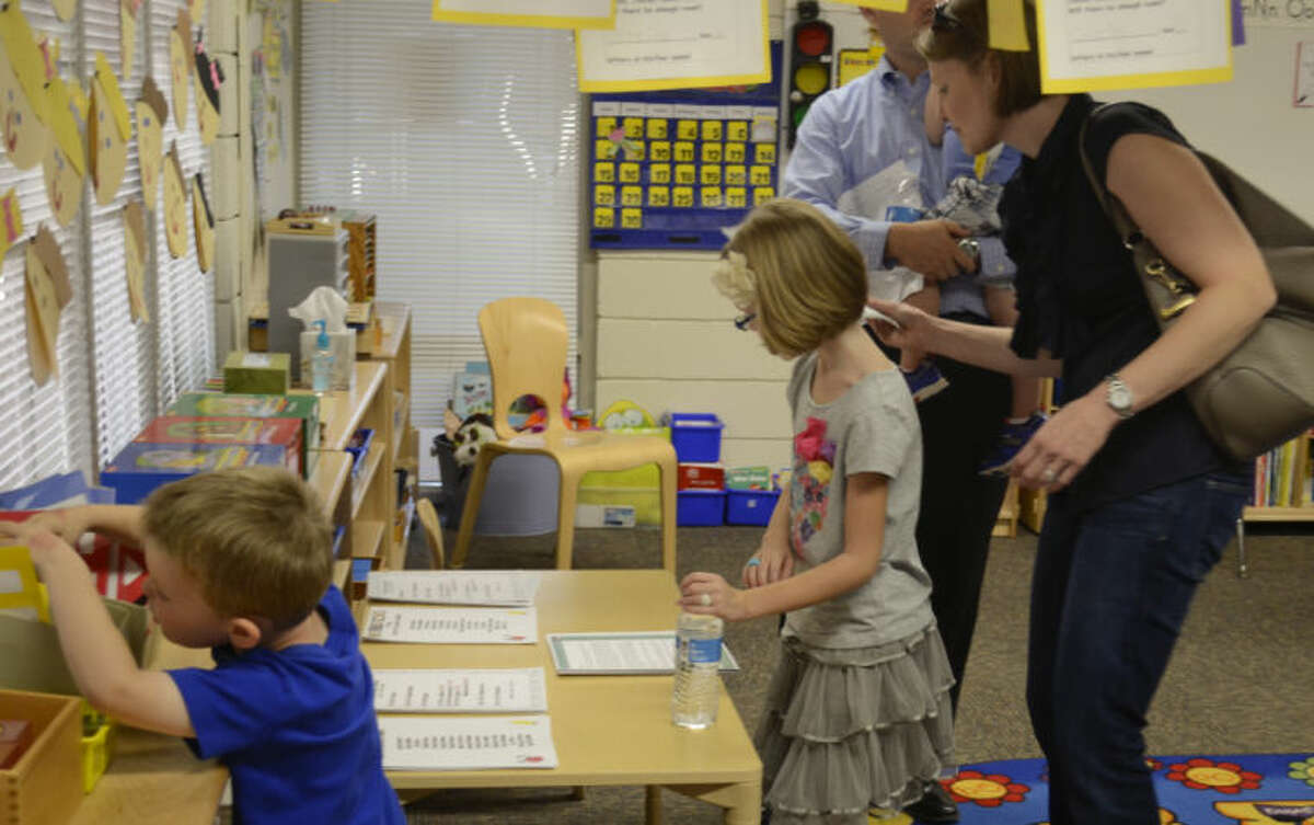 Tyler McDaniel, K4, looks for projects to show his parents, Greg and Devon McDaniel as his sister, Kate, third grade looks over papers Monday during Trinity School open house. Tim Fischer\Reporter-Telegram
