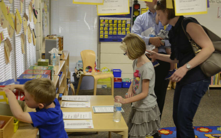 Tyler McDaniel, K4, looks for projects to show his parents, Greg and Devon McDaniel as his sister, Kate, third grade looks over papers Monday during Trinity School open house. Tim Fischer\Reporter-Telegram Photo: Tim Fischer