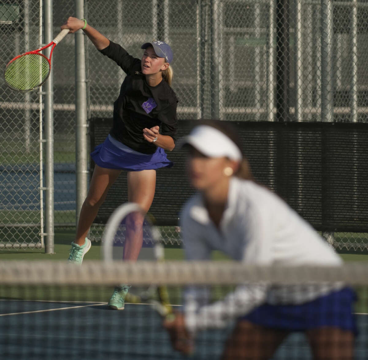 Midland High's Kate Daugherty, black jacket, and Allison Stewart, white jacket, play for the girls doubles championship Friday, 4-10-15, at Bush Tennis Center during the district 3-6A tournament. Tim Fischer\Reporter-Telegram