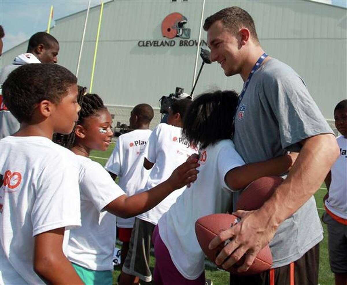 Cleveland Browns' Johnny Manziel gets a hug from a young girl during an NFL football Play 60 youth event at the Cleveland Browns practice facility Friday, June 27, 2014, in Berea, Ohio. The AFC rookies took part in the NFL's annual Rookie Symposium. (AP Photo/Aaron Josefczyk)