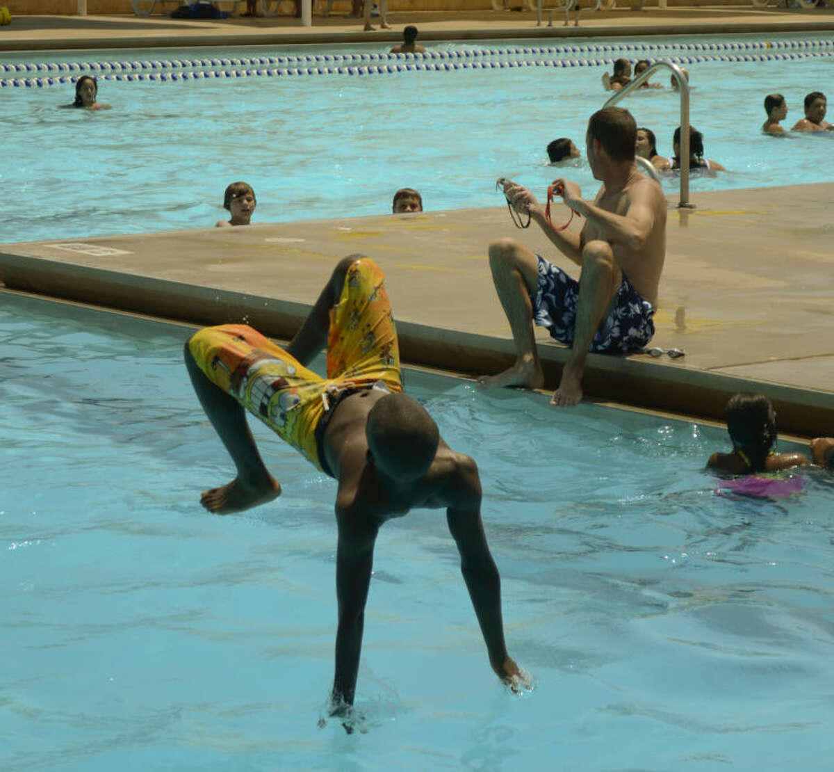 Vidal Flores, 10, nearly makes a flip off the board as temperatures hover around 100, A cool dip in the pool at Doug Russell Monday helped cool some Midlanders off. Tim Fischer\Reporter-Telegram