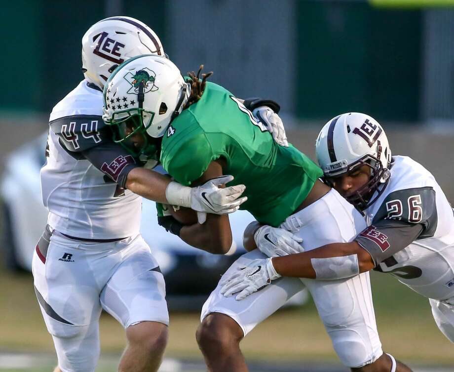Southlake Carroll running back Lil' Jordan Humphrey (4) gets wrapped up by  Lee linebacker Kade Hicks (44) and Kaleb Nunez (26) during the 1st quarter, Friday night, September 11, 2015 played at Dragon Stadium in Southlake. Photo: Steve Nurenberg