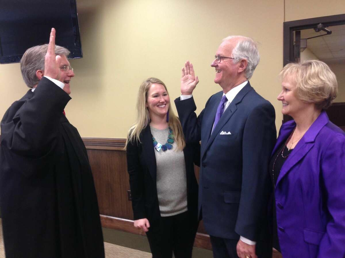 """Retired 318th District Judge Dean Rucker, left, on Jan. 6 swore in County Judge Mike Bradford for a third term. Looking on are Bradord's wife, Ann, far right, and daughter, Lauren. Bradford won the Republican Primary county judge race on March 4 by obtaining 52 percent of the vote. Other county officials were sworn in Tuesday morning by Rucker and 142nd District Judge George """"Jody"""" Gilles."""