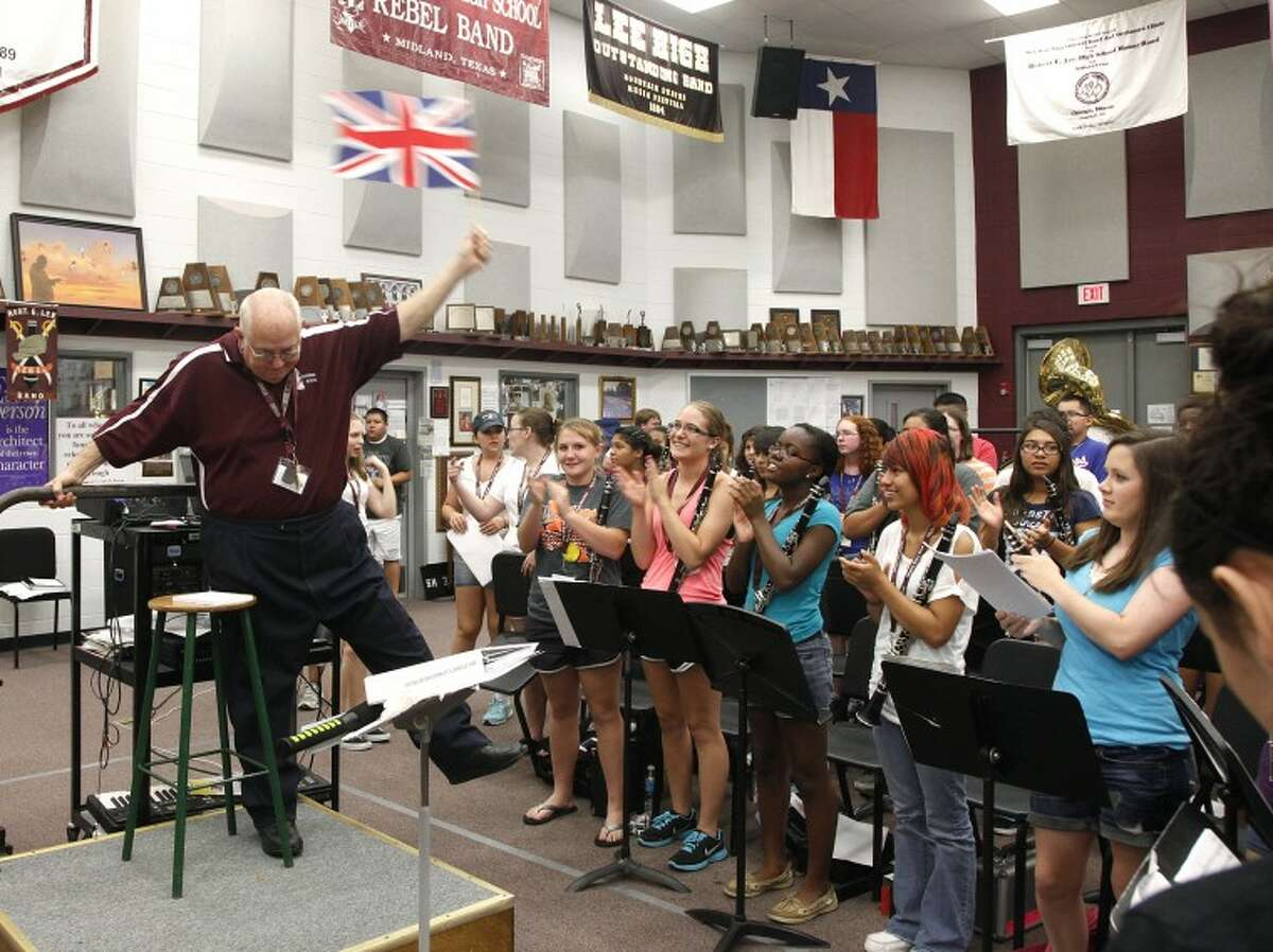 """Lee High School band director Randy Storie waves the British flag to """"Bugler's Dream,"""" one of the Olymipic theme songs, to rouse his students and introduce a talk about training and what that means to his band. Chaney Mitchell/Reporter-Telegram"""