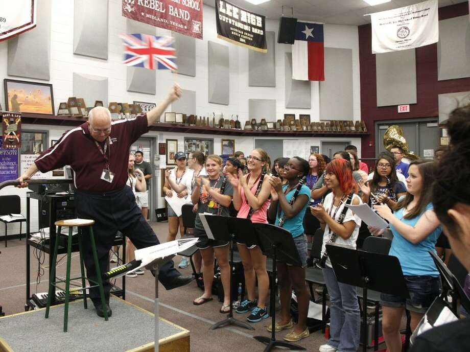 "Lee High School band director Randy Storie waves the British flag to ""Bugler's Dream,"" one of the Olymipic theme songs, to rouse his students and introduce a talk about training and what that means to his band. Chaney Mitchell/Reporter-Telegram Photo: Chaney Mitchell"