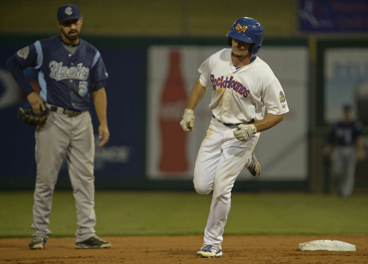 Hounds' Jaycob Brugman makes his way past Hooks' Jio Mier on his way around the bases for a homerun Saturday 9-12-2015 at Security Bank Ballpark. Tim Fischer\Reporter-Telegram