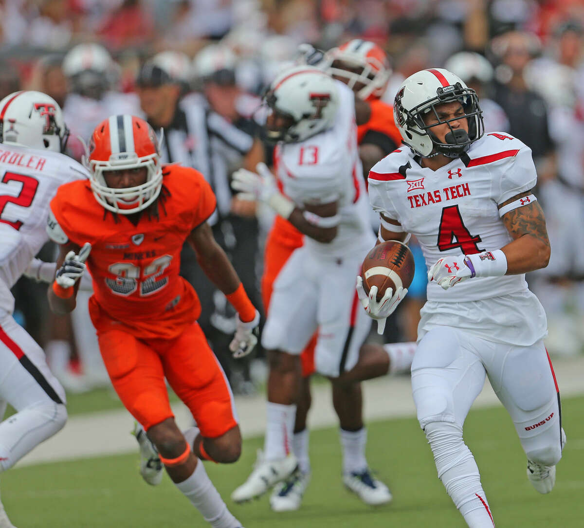 Tech running back Justin Stockton (4) checks over his shoulder to make sure no one is gaining on him as he races to the end zone in Saturday's game with the UTEP Miners.