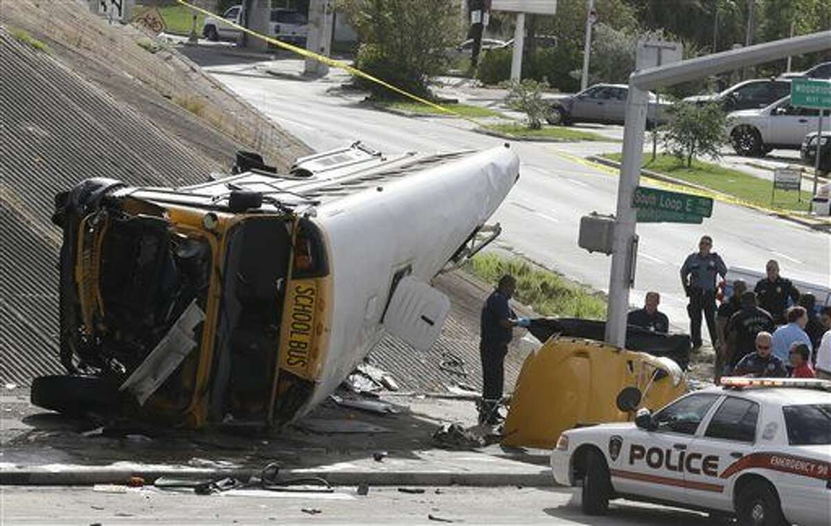 Investigators work around a Houston school bus, right, after it drove off a highway overpass Tuesday, Sept. 15, 2015, in Houston. A female student died at the scene of the wreck and a second girl died at a hospital, according to a statement by the Houston Independent School District. Three others seriously injured (AP Photo/Pat Sullivan)