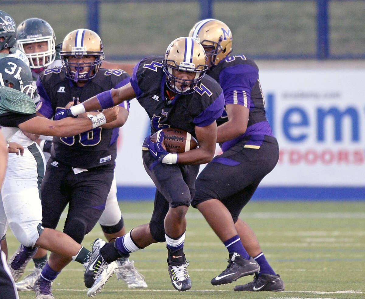 Midland High running back Ricky Hubert (4) breaks through the El Paso Montwood defensive line on Friday, Sept. 4, 2015, at Grande Communications Stadium. James Durbin/Reporter-Telegram