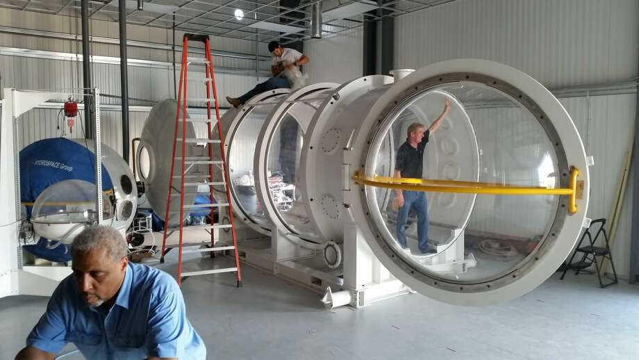 From left, Livingston Holder, Angel Lopez, and Dennis Gilliam around (and inside) the large hypobaric chamber at Orbital Outfitters' new facility at Midland Air & Space Port.