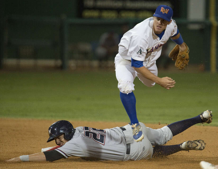 RockHounds' Wade Kirkland jumps over Naturals Alex Liddi to make the double play to first Tuesday 9-15-2015 at Security Bank Ballpark. Tim Fischer\Reporter-Telegram Photo: Tim Fischer