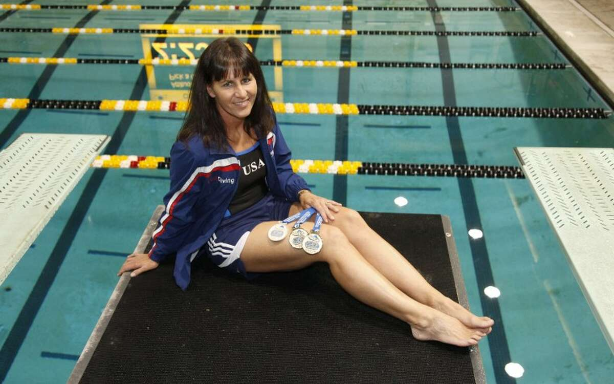 Midland ISD diving coach Jennifer Mangum sits atop the 3-meter diving platform with three medals she won at a diving competition in Italy.