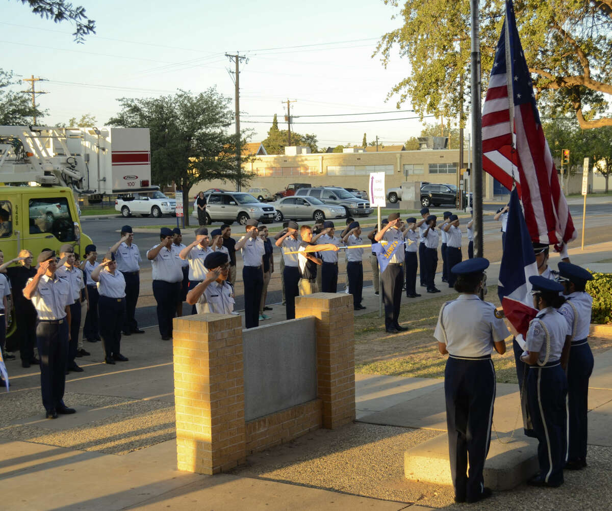 Members of Midland High JROTC salute as the flag is raised Thursday during a 9-11 Remembrance Ceremony. Tim Fischer\Reporter-Telegram