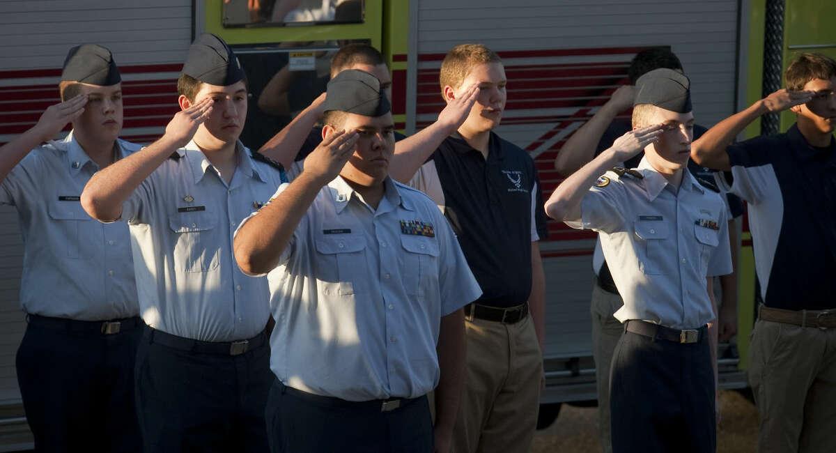 Members of Midland High JROTC salute as the flag