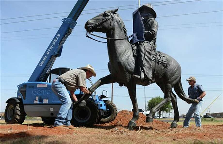 "Sculptor Terrell O'Brien of Fort Davis, Texas, left, and Stephen Dinse, Shidoni foundry manager of Tesuque, New Mexico, move a bronze cowboy sculpture into place where it will be secured to a concrete slab Monday, July 28, 2014 in front of the University of Texas of the Permian Basin in Odessa, Texas. Five steers will be added to complete ""The Days of the Longhorn"" sculpture that was commissioned by the Odessa Council for the Arts and Humanities. (AP Photo/Odessa American, Mark Sterkel) Photo: Mark Sterkel / Odessa American"