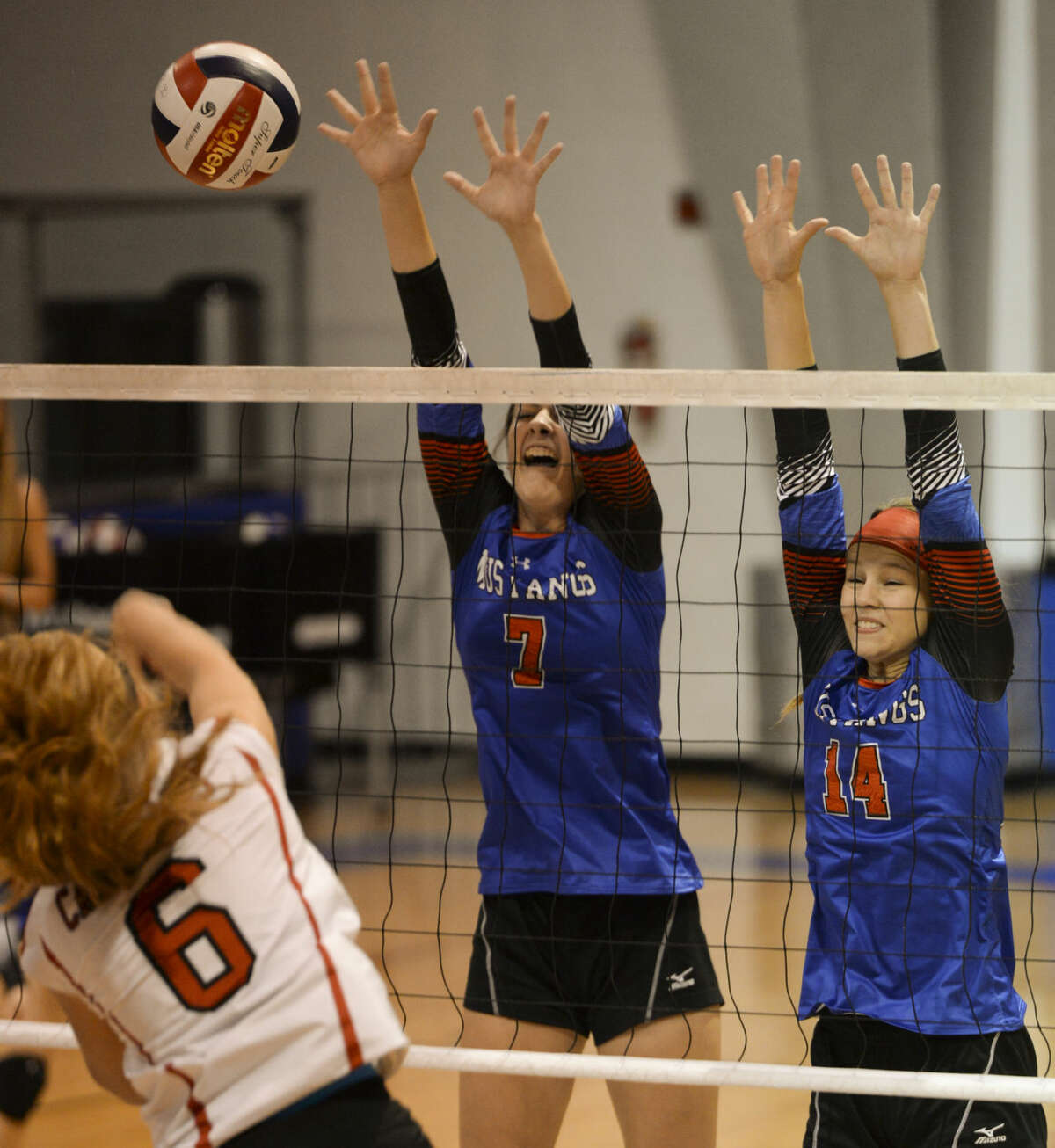 Midland Christian's Emma Holder, 7 and Meaga Thomason, 14, go for the block as Fort Worth Christian's Lauren Rothschadl puts the ball over the net Saturday 9-19-2015 at the McGraw Events Center. Tim Fischer\Reporter-Telegram