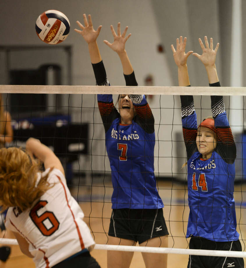 Midland Christian's Emma Holder, 7 and Meaga Thomason, 14, go for the block as Fort Worth Christian's Lauren Rothschadl puts the ball over the net Saturday 9-19-2015 at the McGraw Events Center. Tim Fischer\Reporter-Telegram Photo: Tim Fischer