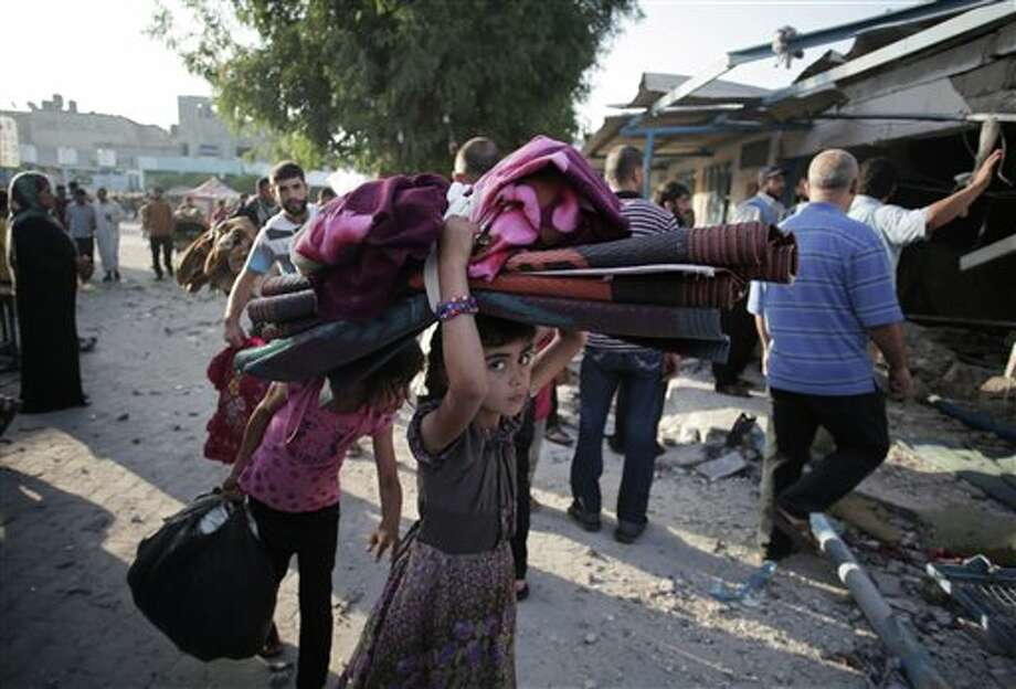 A Palestinian girl carries belongings as she and her family leave the Abu Hussein U.N. school in the Jebaliya refugee camp, northern Gaza Strip, hit by an Israeli strike earlier, on Wednesday, July 30, 2014. Several Israeli tank shells slammed into the crowded U.N. school used as shelter for refugees in the Gaza war early on Wednesday, a Palestinian health official and a U.N. official said. (AP Photo/Khalil Hamra) Photo: Khalil Hamra / AP