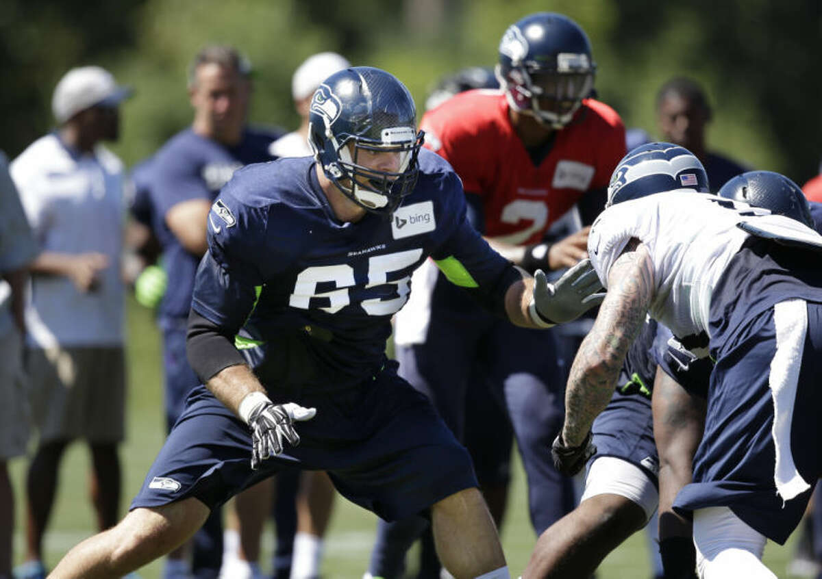 Seattle Seahawks' Eric Winston (65) moves to block at the line of scrimmage at an NFL football camp practice Tuesday, July 29, 2014, in Renton, Wash. (AP Photo/Elaine Thompson)