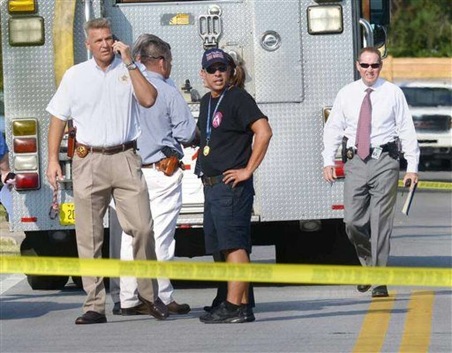 Okaloosa County Sheriff Larry Ashley, far left, and other sheriff's office personnel and emergency responders work at the scene of a law office in Shalimar, Fla., where a deputy sheriff was shot Tuesday, Sept. 22, 2015. The suspect then fled to the nearby town of Niceville and barricaded himself in a hotel before exchanging gunfire with deputies. He was taken into custody just before 10:30 a.m. Central time. (Devon Ravine/Northwest Florida Daily News via AP) Photo: Devon Ravine