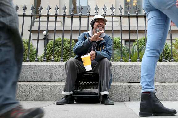 Barry Hewett, a panhandler who sits in front of the historic Old Mint building on Fifth St. greets passers by with a wave or salute nearly every morning in San Francisco, California on thursday, may 5, 2016.