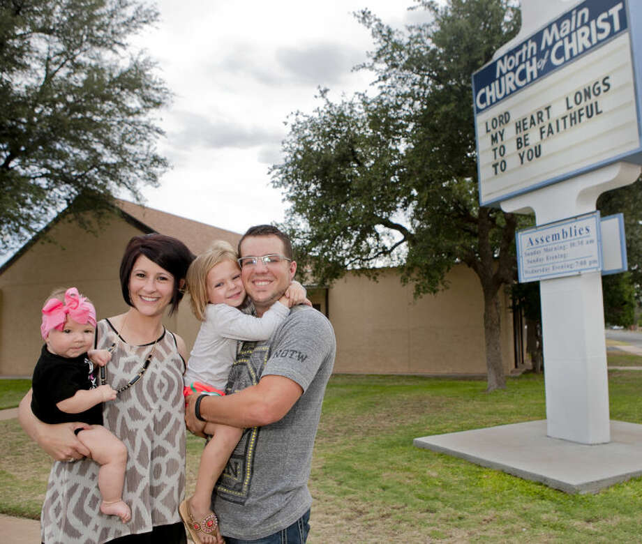 Adam Elliott, minister at Main Street Church of Christ, stands with his family from left, 6-month-old Quinn, wife Lindsay Elliott, and 4-year-old Capri, outside Main Street Church of Christ on Tuesday. James Durbin/Reporter-Telegram Photo: James Durbin