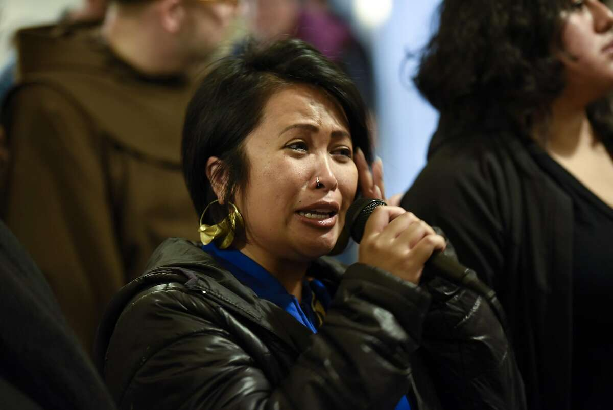 Jo Cruz of San Francisco wipes away tears as she speaks in support of protesters supporting the