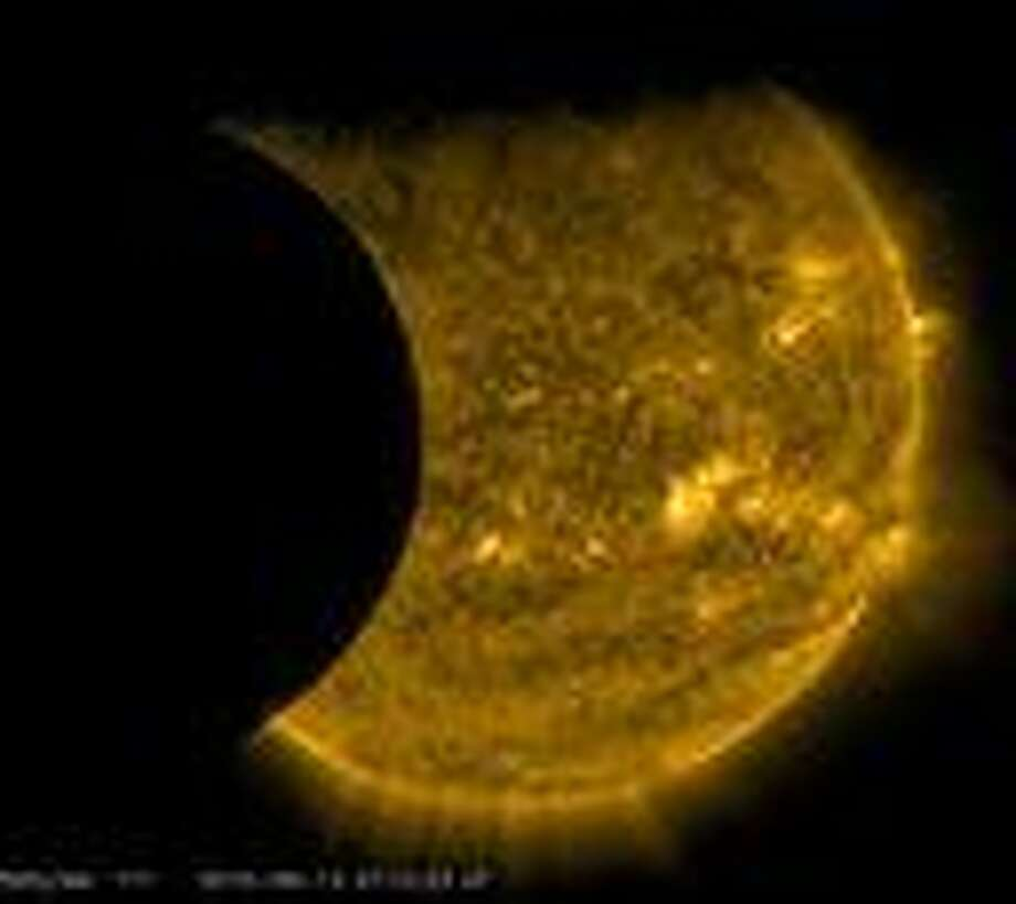 This Sept. 13, 2015 image provided by NASA shows the moon, left, and the Earth, top, transiting the sun together, seen from the Solar Dynamics Observatory. The edge of Earth appears fuzzy because the atmosphere blocks different amounts of light at different altitudes. This image was taken in extreme ultraviolet wavelengths, invisible to human eyes, but here colorized in gold. A total lunar eclipse will share the stage with a so-called supermoon Sunday evening, Sept. 27, 2015 as seen from the United States. That combination hasn't been seen since 1982 and won't happen again until 2033. (NASA/SDO via AP) Photo: HOGP