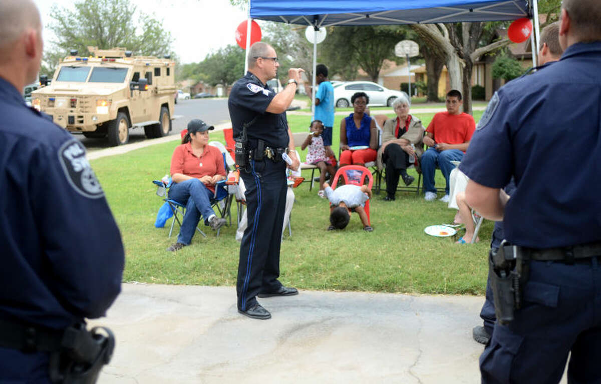 (File Photo) Midland Police Officer David Scardino talks with neighborhood families during National Night Out on Tuesday. James Durbin/Reporter-Telegram