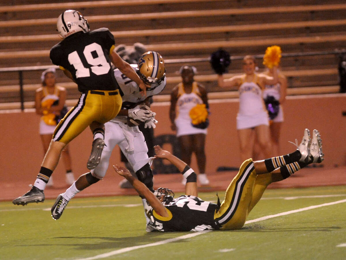 Midland High receiver Courtney McMaryion brings in a 48-yard reception between Roy Haden, left, and Nate Martinez of Amarillo High Friday, September 25, 2015 at Dick Bivins Stadium. (Sean Steffen / Amarillo Globe-News)